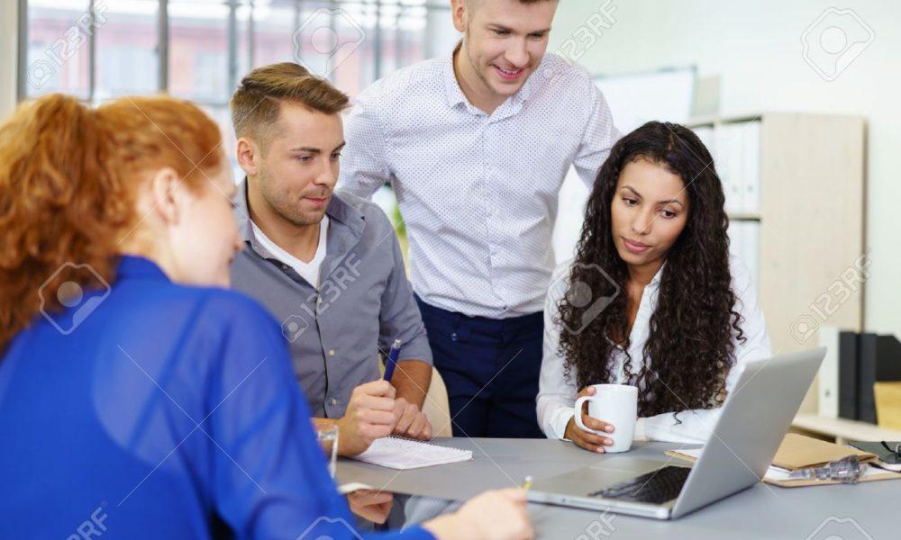 48562291-grupo-de-los-cuatro-jóvenes-empresarios-viendo-algo-en-el-ordenador-portátil-mientras-que-haciendo-una-re